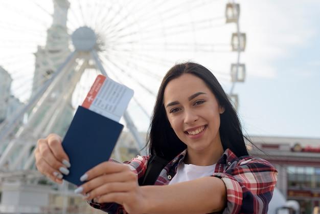 Portrait de femme souriante montrant un billet d'avion et un passeport