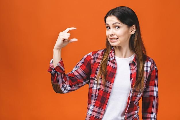 Portrait de femme souriante montrant une petite quantité de quelque chose, isolé sur fond orange.