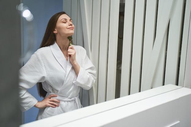 Portrait d'une femme souriante avec un outil de massage debout devant le miroir de la salle de bain