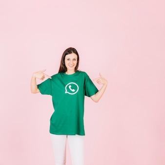 Portrait d'une femme souriante pointant sur son t-shirt avec l'icône de whatsapp