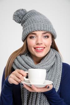 Portrait d'une femme souriante portant une écharpe et un chapeau tenant une tasse avec du café isolé sur fond blanc