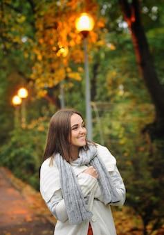 Portrait d'une femme souriante portant une veste en tricot.