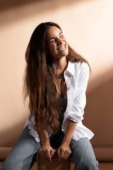 Portrait de femme souriante posant dans une chemise blanche