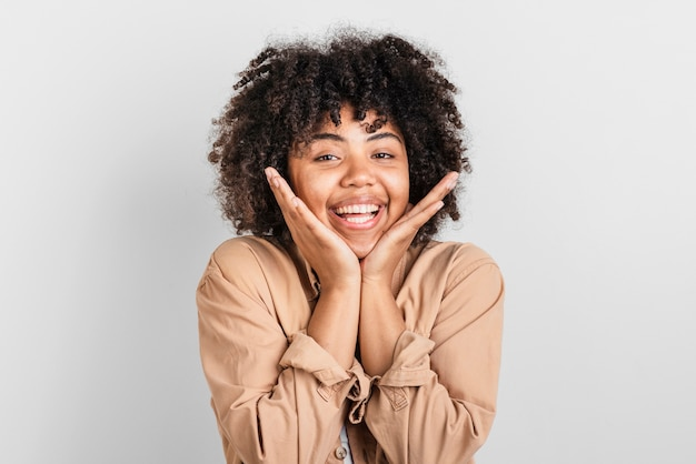 Portrait de femme souriante posant la main autour de son visage