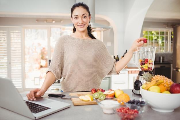 Portrait, de, femme souriante, préparer, jus de fruit, pendant, travaillant, sur, ordinateur portable