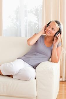 Portrait d'une femme souriante profitant de la musique dans son salon