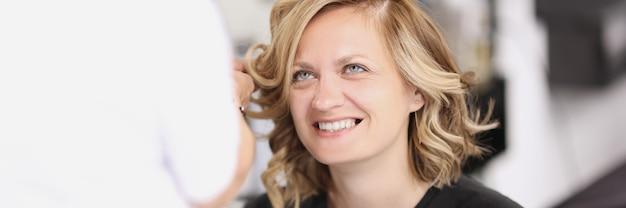 Portrait de femme souriante qui se fait coiffer à partir de boucles