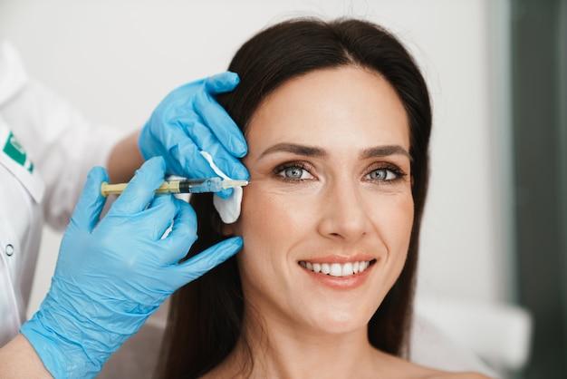 Portrait d'une femme souriante recevant un traitement de mésothérapie au visage par un spécialiste des gants dans un salon de beauté