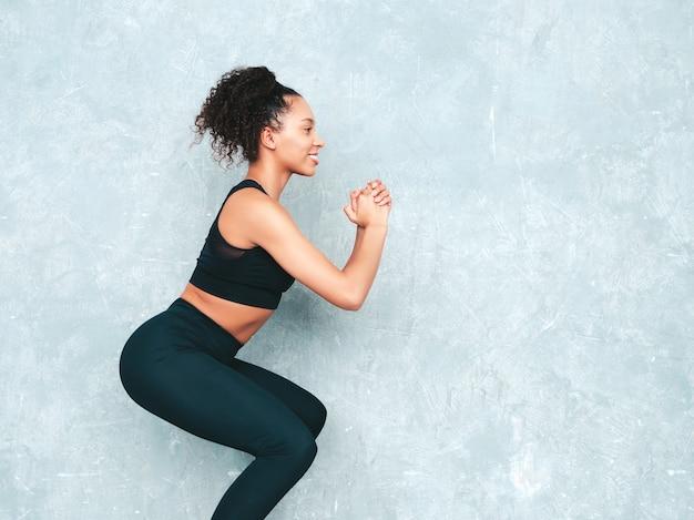 Portrait de femme souriante de remise en forme en vêtements de sport avec une coiffure afro curls