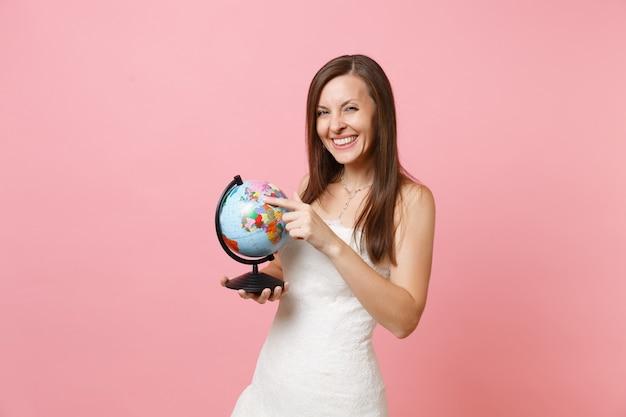 Portrait d'une femme souriante en robe blanche en dentelle tenant un globe terrestre, choisissant le lieu, le pays, les vacances