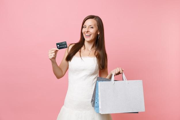 Portrait d'une femme souriante en robe blanche tenant des sacs de paquets multicolores par carte de crédit avec des achats après le shopping