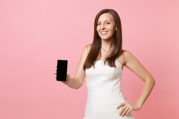 Portrait de femme souriante en robe blanche tenant un téléphone portable avec un écran vide noir vierge