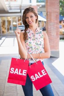 Portrait de femme souriante avec des sacs à provisions de vente montrant la carte de crédit