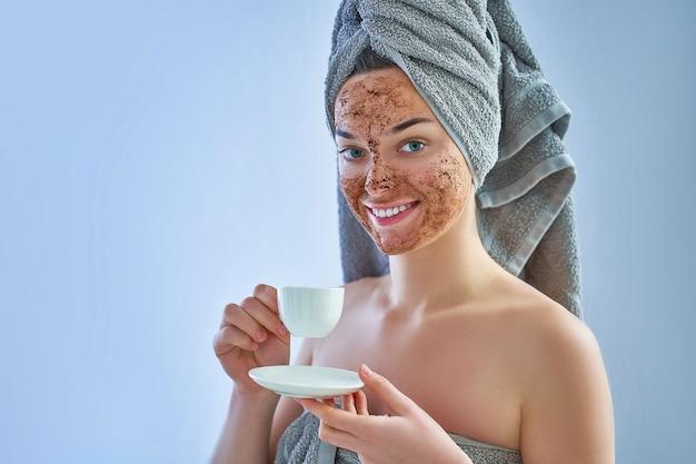 Portrait de femme souriante en serviette de bain avec masque naturel gommage au café après la douche