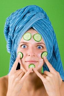 Portrait de femme souriante en serviette bleue et masque de concombre sur fond vert