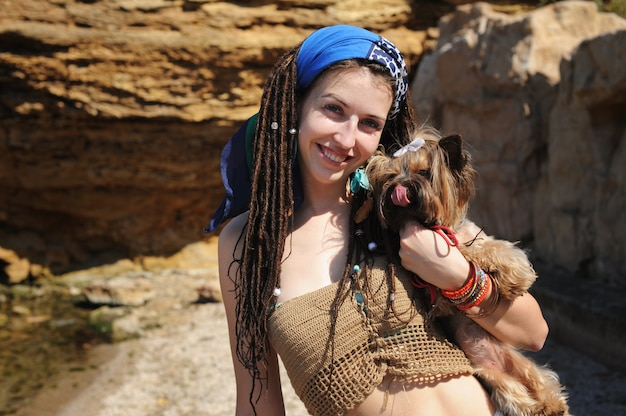 Portrait de femme souriante avec son chien yorkshire terrier, fille avec des dreadlocks