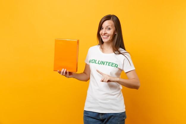 Portrait de femme souriante en t-shirt blanc avec inscription écrite bénévole titre vert tenir une boîte en carton orange isolée sur fond jaune. aide d'assistance gratuite volontaire, concept de grâce de charité