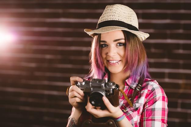 Portrait de femme souriante tenant une caméra vintage