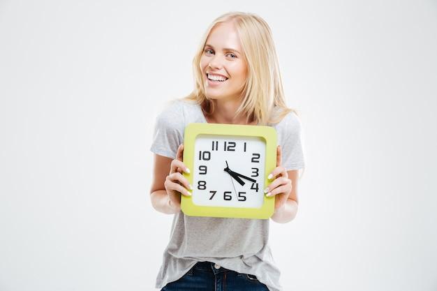 Portrait d'une femme souriante tenant une horloge murale isolée sur un mur blanc