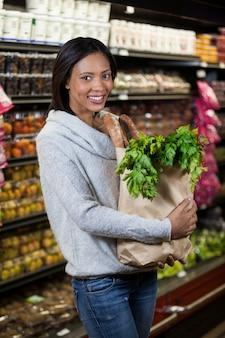 Portrait de femme souriante tenant un sac d'épicerie