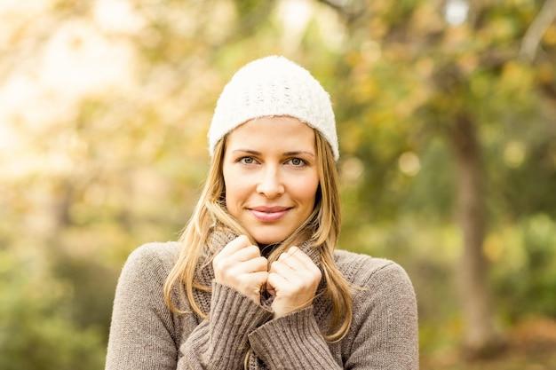 Portrait de femme souriante tenant son foulard un jour d'automne