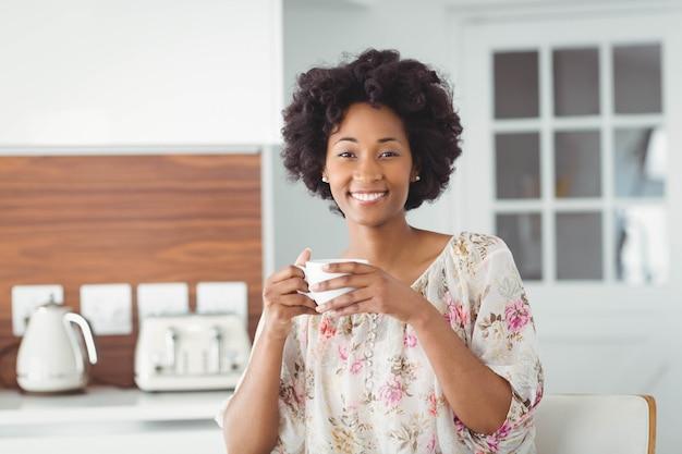 Portrait de femme souriante tenant une tasse blanche dans la cuisine