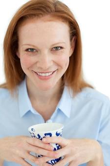 Portrait d'une femme souriante tenant une tasse de thé