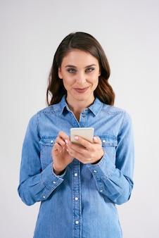 Portrait de femme souriante tenant un téléphone portable