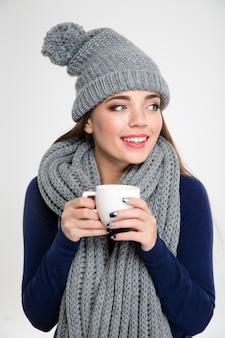 Portrait d'une femme souriante en tissu d'hiver tenant une tasse de café et regardant loin isolé sur fond blanc