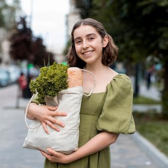 Portrait de femme souriante transportant des produits d'épicerie