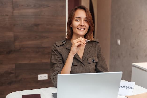 Portrait de femme souriante travaillant à la maison et regardant la caméra