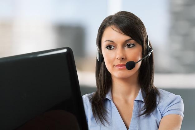 Portrait d'une femme souriante utilisant un casque devant son ordinateur