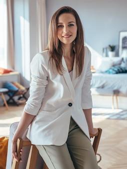 Portrait de femme souriante en veste blanche debout appuyé sur une chaise.