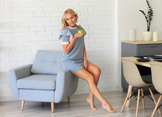 Portrait, femme, sourire, séance, fauteuil, tenue, pomme verte, main