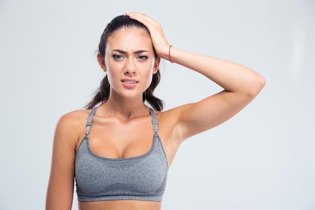 Portrait d'une femme sportive ayant des maux de tête isolé sur un mur blanc