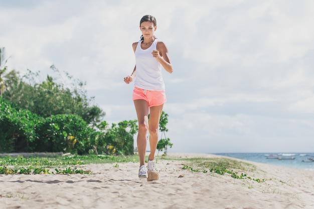 Portrait de femme sportive jogging à la plage