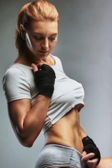 Portrait de femme sportive en tenue de sport sombre sur fond gris