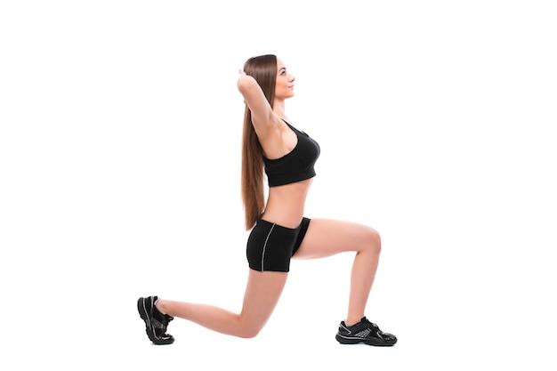 Portrait de femme sportive en tenue de sport travaillant, faisant des exercices isolés sur fond blanc