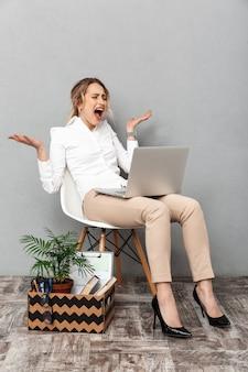 Portrait de femme stressée à l'aide d'un ordinateur portable alors qu'il était assis dans une chaise avec des choses de bureau, isolé