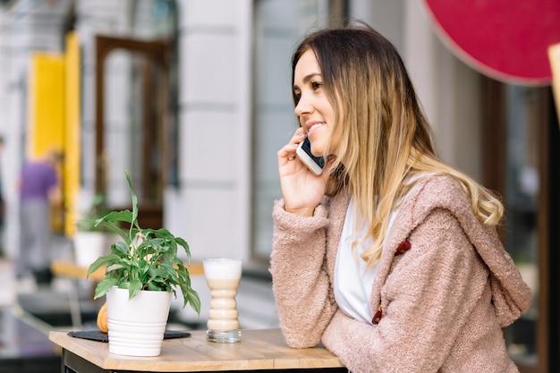 Portrait de femme de style jeune est assis dans la cafétéria dans la rue