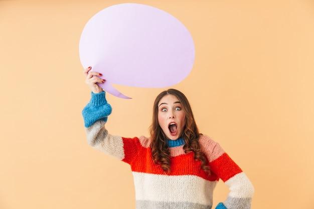 Portrait de femme surprise de 20 ans tenant une bulle de pensée vide au-dessus de sa tête, fond pour votre texte, en position isolée