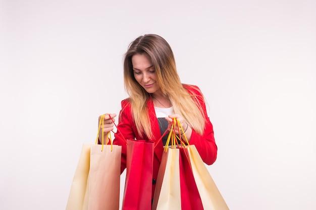 Portrait de femme surprise en costume rouge avec des sacs à provisions.