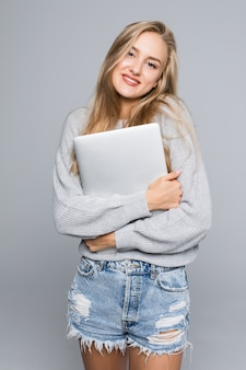 Portrait de femme surprise heureuse debout avec ordinateur portable isolé sur fond gris