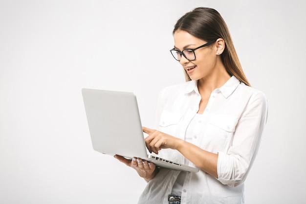 Portrait de femme surprise heureuse debout avec ordinateur portable