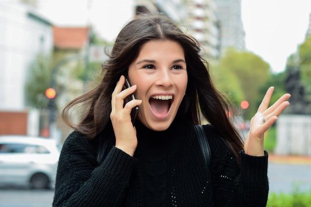 Portrait d'une femme surprise parlant sur un téléphone intelligent