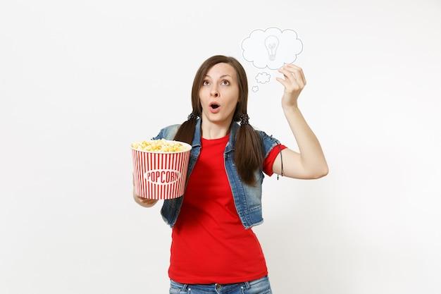 Portrait d'une femme surprise en vêtements décontractés en regardant un film, tenant un nuage avec une ampoule, une idée et un seau de pop-corn isolé sur fond blanc. émotions dans le concept de cinéma. bulle