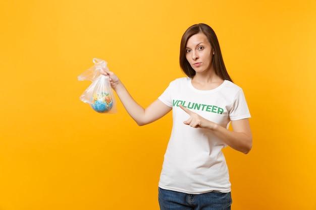 Portrait de femme en t-shirt blanc inscription écrite titre vert volontaire tenir dans un sac en plastique globe terrestre isolé sur fond jaune. aide d'assistance gratuite volontaire, concept de grâce de charité.