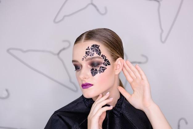 Portrait femme avec tatouage de lierre noir autour de ses yeux avec strass