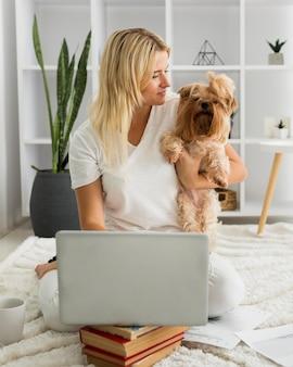 Portrait de femme tenant un chien tout en travaillant à domicile