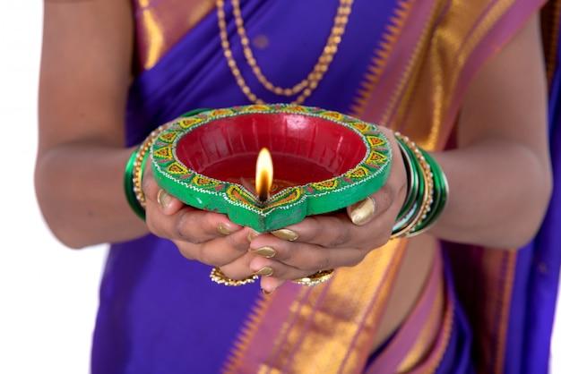 Portrait d'une femme tenant diya, diwali ou deepavali photo avec des mains féminines tenant une lampe à huile pendant le festival de la lumière sur le mur blanc